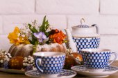 Eastern exposition of Eastern cake, colorful eastern eggs and violet snowdrop with vintage Russian cup of tea and kettle on wooden table nad white brick background. Happy Eastern.