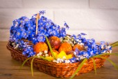 Exposition in the basket violet snowdrop whit flower frezia and Eastern eggs on wooden table and white brick background.