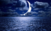 Crescent moon over the sea at night