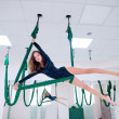 A girl with long dark hair is trained in a green h...