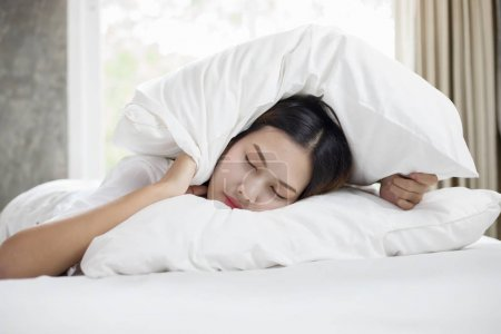 Photo for Asian woman hates waking up early in the morning. Sleepy girl looking at alarm clock and trying to hide under the pillow - Royalty Free Image