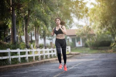 Photo for Running woman. Female runner jogging during outdoor  on road .Young mixed race girl jogging - Royalty Free Image