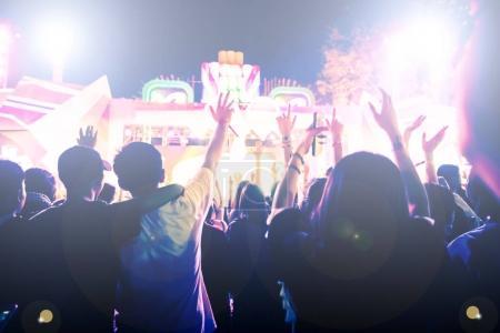 Photo pour Silhouettes de foule de concert en vue de l'arrière du festival foule levant leurs mains sur les lumières de la scène lumineuse - image libre de droit