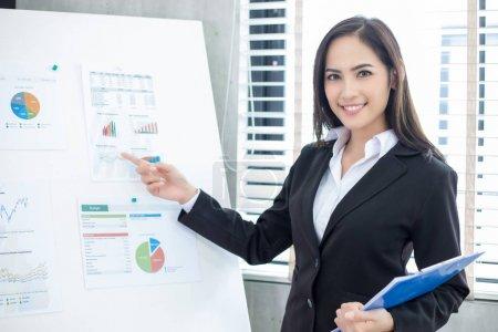 Photo pour Femmes d'affaires asiatiques et groupe utilisant un cahier pour les partenaires d'affaires discuter des documents et des idées à la réunion et les femmes d'affaires souriant heureux de travailler - image libre de droit