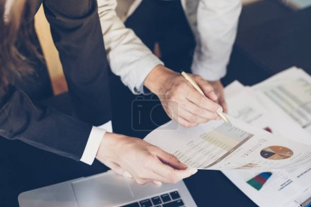 Photo for Asian businesswomen holding a pen and analysis documents on office table with laptop computer and graph financial diagram working in the background - Royalty Free Image