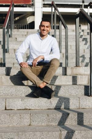 Photo for Young smiling mixed race man sitting on the staircase outside - Royalty Free Image