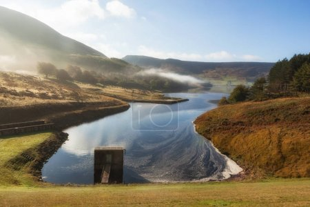 Photo for Spillway at Dove stones reservoir with slightly mist and blue sky, Oldham, Saddleworth, UK - Royalty Free Image