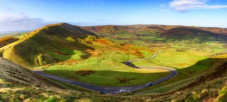 Long and winding rural road of Winnat Pass leading through green hills in Peak District, United Kingdom.