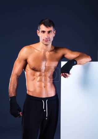 Muscular man holding blank