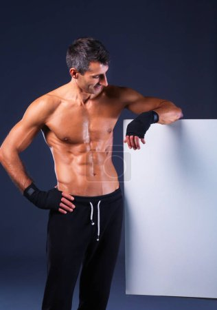 muscular man holding blank