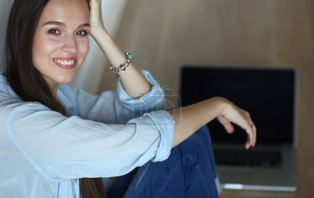 Photo for Young beautiful woman at home sitting on the floor with laptop - Royalty Free Image