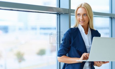 Successful female office worker with net-book is standing in skyscraper interior against big window