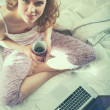 Young beautiful woman sitting in bed with laptop....