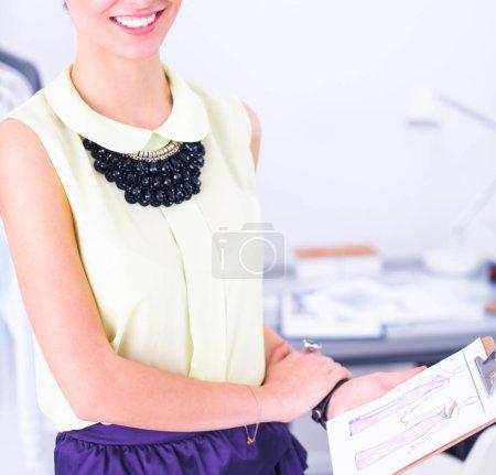 Modern young fashion designer working at studio...