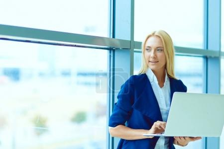 Businesswoman standing against office window holding laptop. Businesswoman