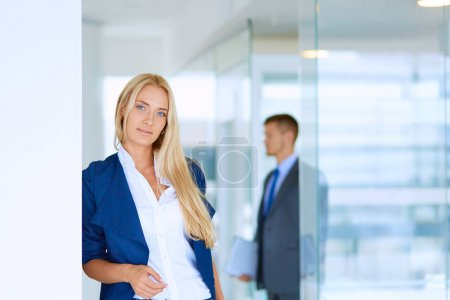 Businesswoman standing against office window talking on mobile phone . Businesswoman
