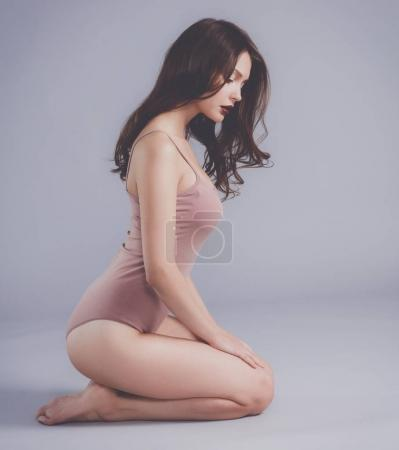 Photo for Beautiful barefoot woman sitting on the floor. - Royalty Free Image