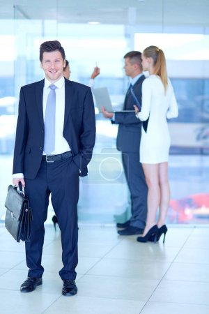 Portrait of young businessman in office with colleagues in the background . Portrait of young businessman.