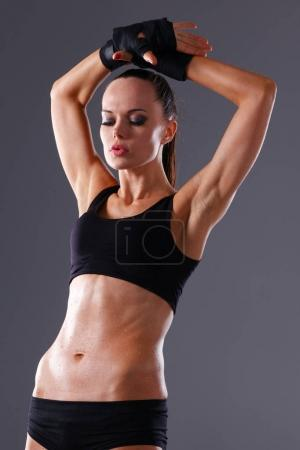 Muscular young woman standing on gray background. Muscular young woman