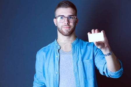 Young man holding a credit card standing on gray background. Young entrepreneur.