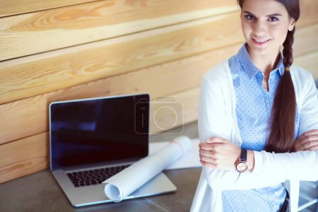 Young female standing near desk at home. The woman at the table. Workplace.