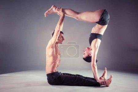 Photo pour Jeune couple pratiquant l'acro yoga sur tapis en studio ensemble. Acroyoga. Du yoga. Yoga partenaire - image libre de droit