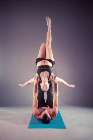 Photo pour Jeune couple pratique du yoga acro sur tapis en studio ensemble. Acroyoga. Yoga du couple. Yoga partenaire - image libre de droit