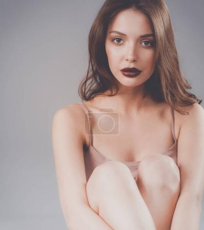 Beautiful barefoot woman sitting on the floor