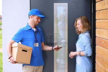 Photo for Smiling delivery man in blue uniform delivering parcel box to recipient - courier service concept. - Royalty Free Image