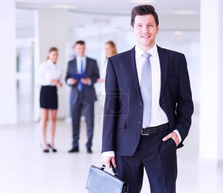 Foto de Retrato de joven empresario en oficina con colegas en el fondo - Imagen libre de derechos