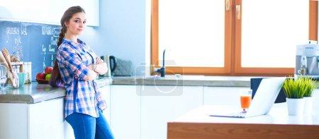 Photo pour Portrait de jeune femme debout avec les bras croisés sur fond de cuisine. - image libre de droit