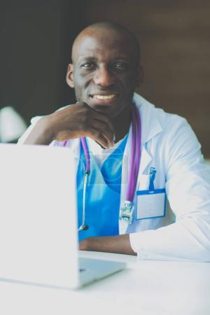 Photo for Young african doctor working on laptop at desk. - Royalty Free Image
