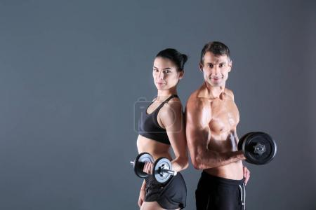 Athletic man and woman with a dumbells. Personal fitness instructor. Personal training.