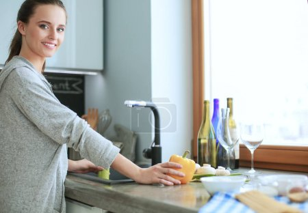 Photo for Beautiful young woman washing vegetables for salad while standing in the kitchen - Royalty Free Image