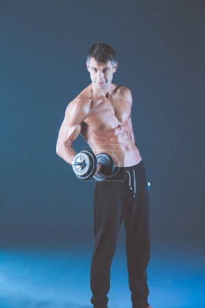 Handsome muscular man working out with dumbbells. Personal fitness instructor. Personal training.