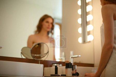 Photo pour Jeune femme regardant dans le miroir et se maquillant - image libre de droit