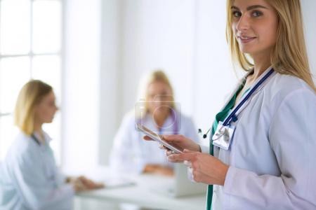 Photo pour Portrait d'une jeune femme médecin, avec aipads à la main, dans un cabinet médical. - image libre de droit