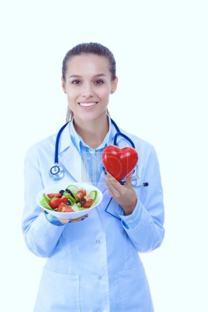 Photo for Portrait of a beautiful woman doctor holding a plate with fresh vegetables and red heart. Woman doctors - Royalty Free Image