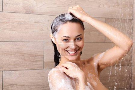 Photo pour Jeune femme belle sous la douche dans la salle de bain - image libre de droit