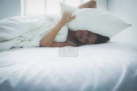 Young caucasian woman covering her head and ears with pillows
