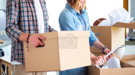 Photo for Couple unpacking cardboard boxes in their new home. Young couple - Royalty Free Image