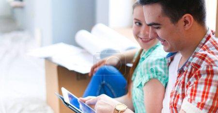 Photo pour Couple déménageant dans la maison assis sur le sol avec ipad. Couple . - image libre de droit