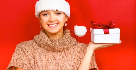 Santa girl holding Christmas gift on red background
