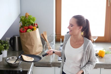 Photo for Young woman prepares pancakes in the kitchen while standing near the table. Woman in the kitchen. Cooking at kitchen - Royalty Free Image