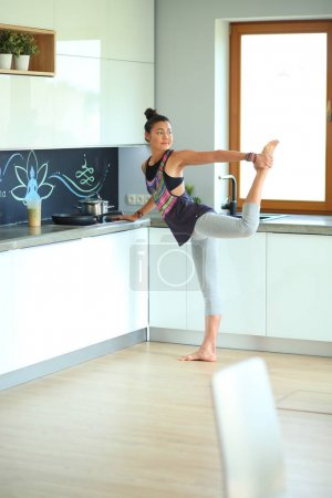 Fitness girl cooking healthy food in the kitchen....