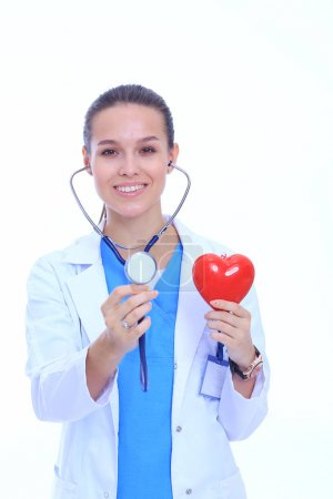Positive female doctor standing with stethoscope and red heart symbol isolated. Woman doctor