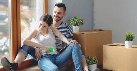 Photo pour Couple emménageant dans la maison assis sur le sol. Couple  . - image libre de droit