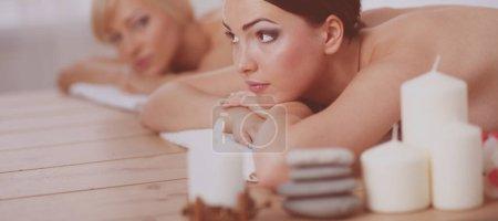Photo pour Deux belles amies allongées sur des tables de bois la tête sur des serviettes attendant leur massage dans le spa. - image libre de droit