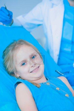 Photo pour Petite fille assise dans le Bureau de dentistes - image libre de droit