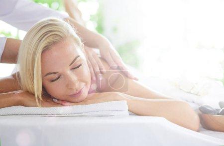 Photo pour Belle jeune femme détendant pendant le massage complet de corps au spa. - image libre de droit